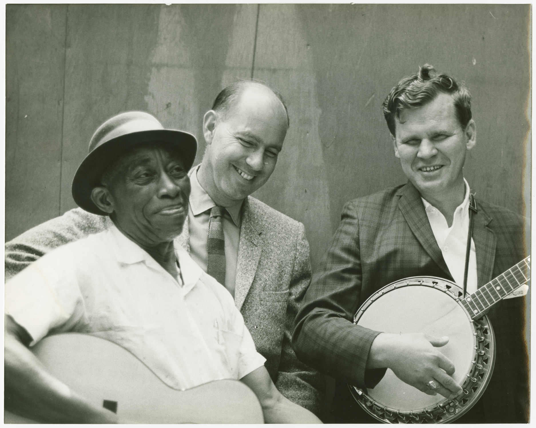 "A photograph showing ""Mississippi"" John Hurt holding a guitar, Sam Hinton, and Arthel ""Doc"" Watson holding a banjo at the Berkeley Folk Music Festival, 1964"