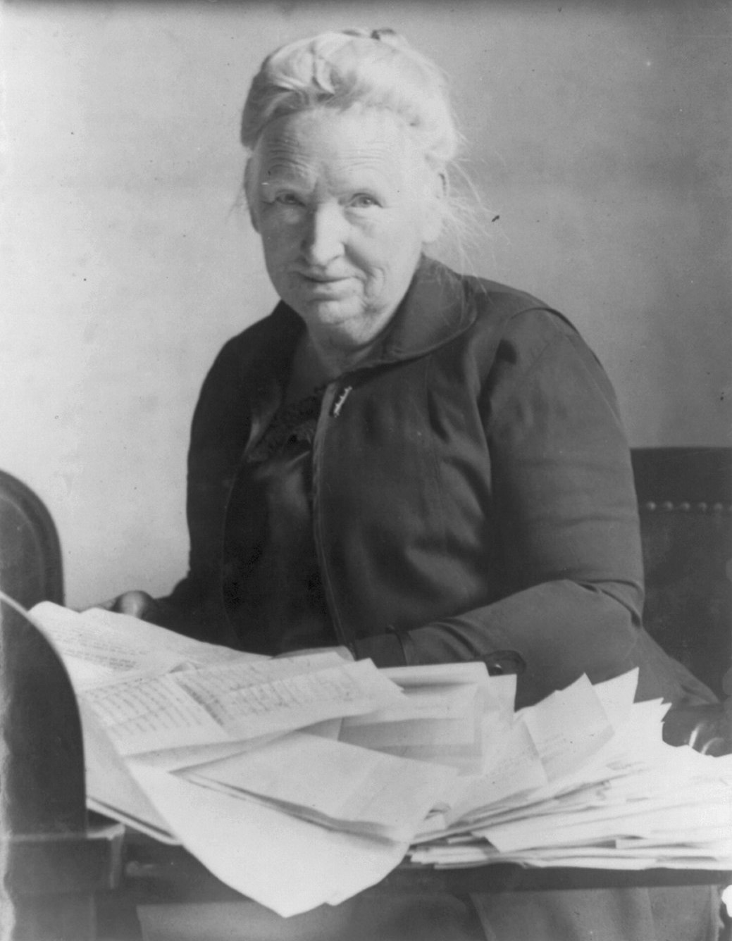 Photograph of Alice Robertson in old age, seated with papers on a table in front of her.