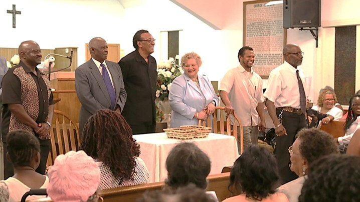 Photograph of Shankeville's 2014 Annual Homecoming event, with Homecoming presidents from Jasper and Newton County settlements standing at the front of a church, and Homecoming attendees seated around them.